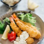 Three panko fried shrimps on a round plate with green salad, a tomato and a wedge of lemon and tartat sauce