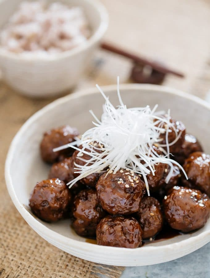 Teriyaki Meatballs served in a Japanese pottery bowl garnished with thinly sliced sacllions