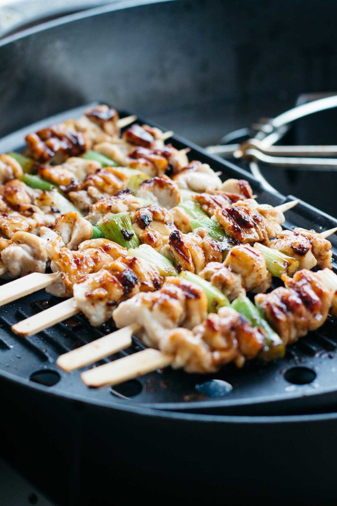 Chicken skewers are being grilled over portable bbq