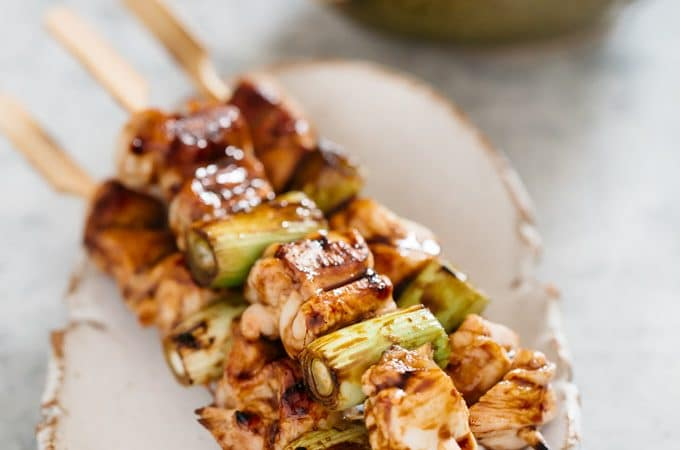 Three Yakitori skewers on Japanese pottery plate with a bowl of yakitori sauce in background