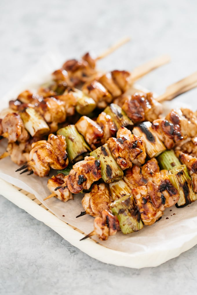 many skewers of Yakitori chicken are piled up on a bamboo tray