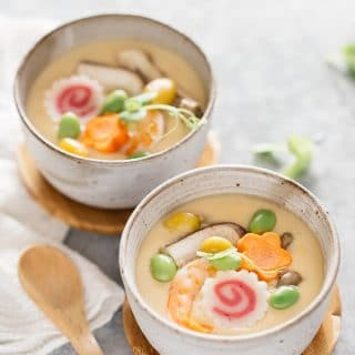Two Chawanmushi bowls with a wooden spoon in back ground.