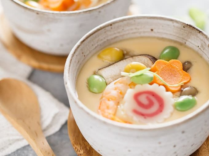 two chawanmushi in bowls with a wooden spoon