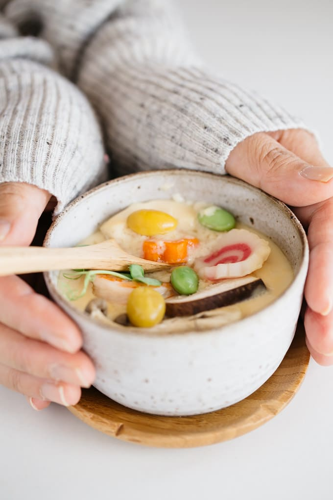 a chawanmushi bowl holded by two hands and a wooden spoon