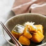 kabocha no nimono served on a round plate with a pair of chopstick