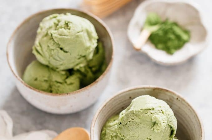 two bowls of green tea ice cream with a wooden spoon and green tea powder in a small bowl with matcha bamboo whisk in background