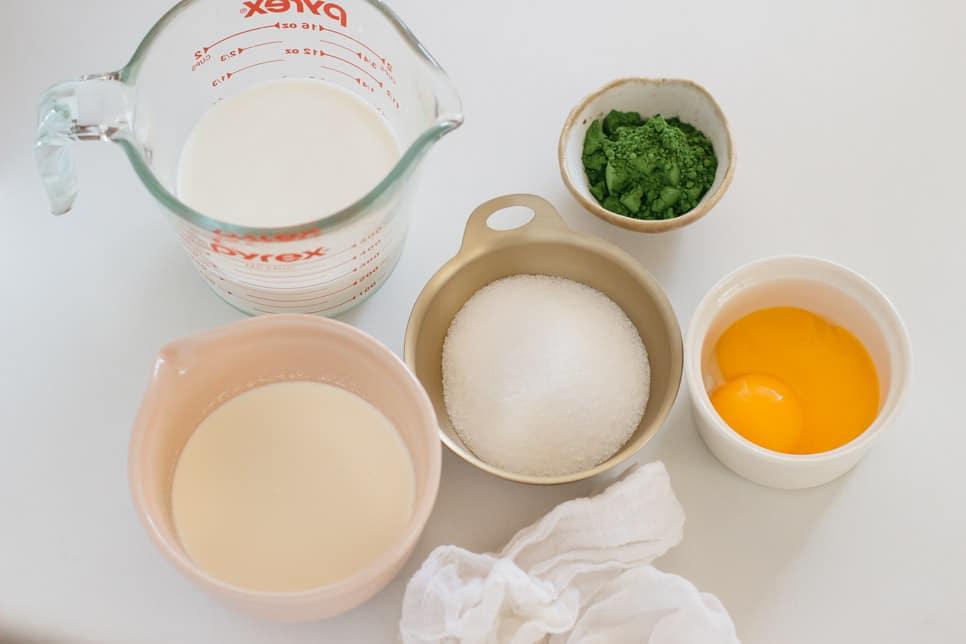 A jug of milk, a bowl of cream, a bowl of sugar, a small bowl of matcha powder, two egg yolks
