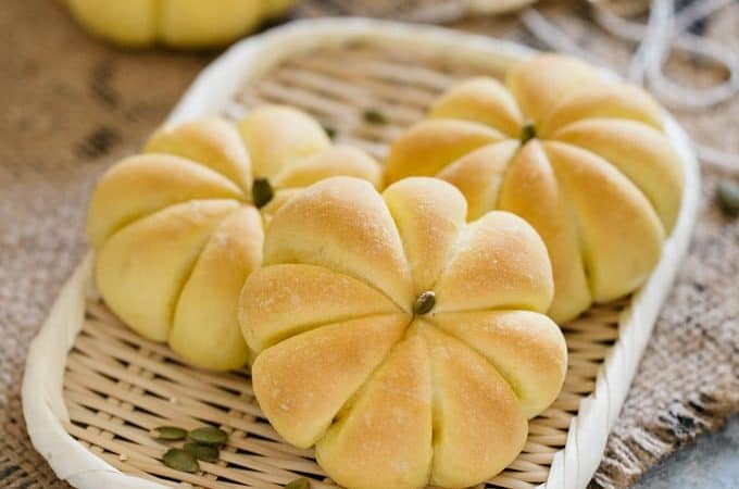 3 Kabocha pumpkin shaped bread rolls on a bamboo tray