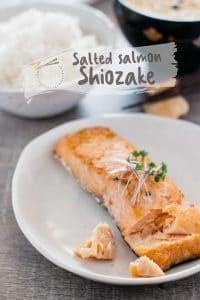 a grilled slated salmon on a round plate with a bowl of plain steamed rice in background