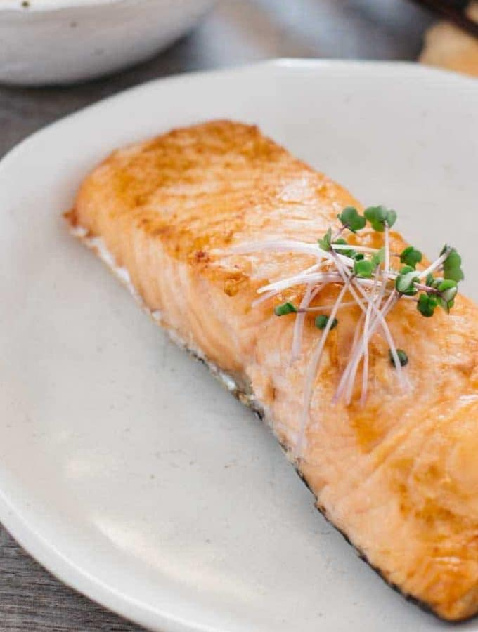 a piece of grilled slated salmon on a white plate