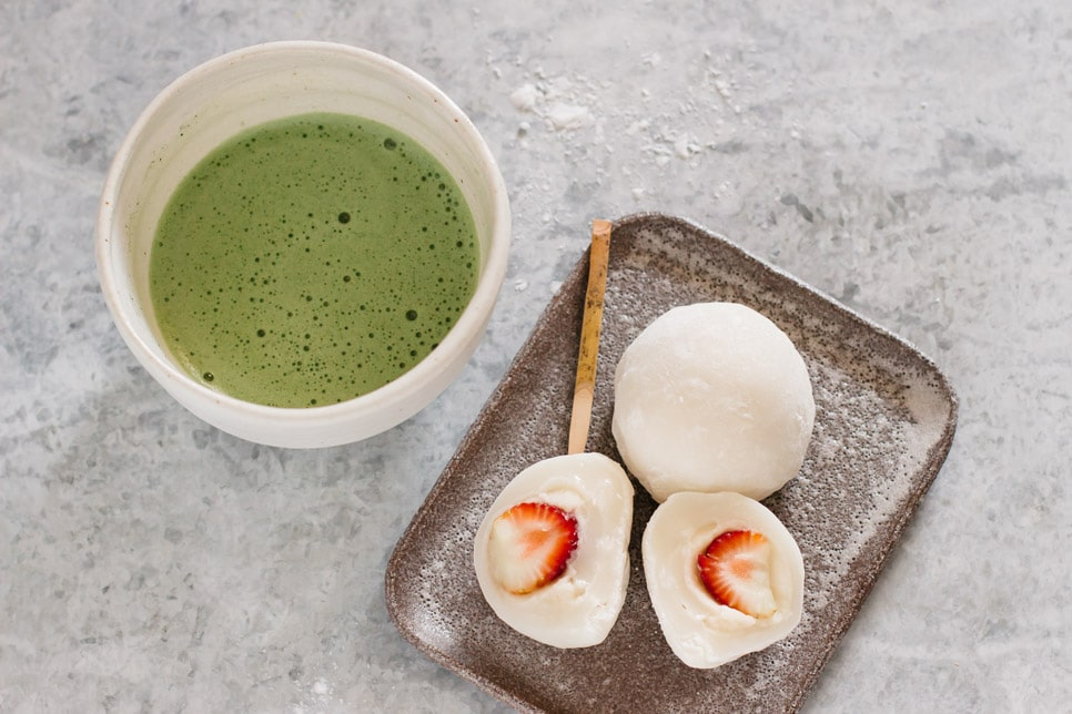 two strawberry mochi on a rectangle shaped plate served with a bowl of matcha green tea