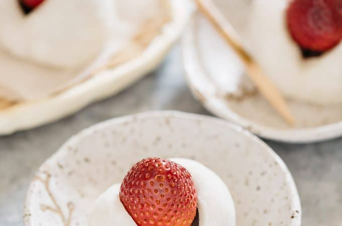 one strawberry mochi on a small plate and in the background too.