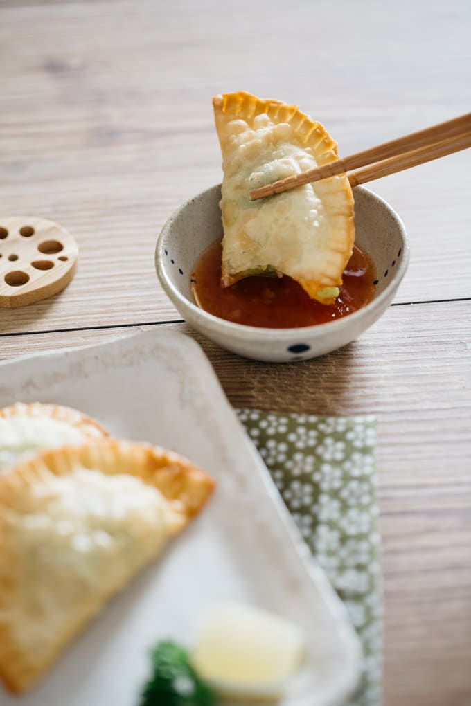 one deep fried gyoza is dipped in a small bowl of sweet chili sauce