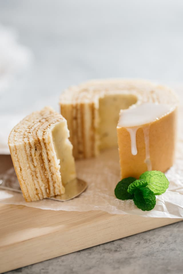 Tree ring shaped Baumkuchen sliced and one piece being taking out with sugar icing over