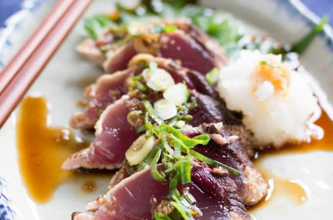 sliced katsuo tataki(bonito) with ponzu sauce on an oval plate