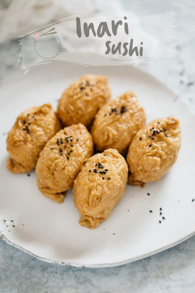 6 inari sushi on a white plate with black sesame seeds sprinkled over