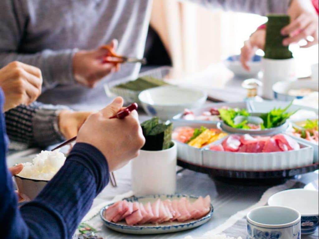 A family enjoying hand roll sushi making themselves at the table