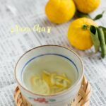 Yuzu Cha served in a small tea bowl and three yuzu citrus