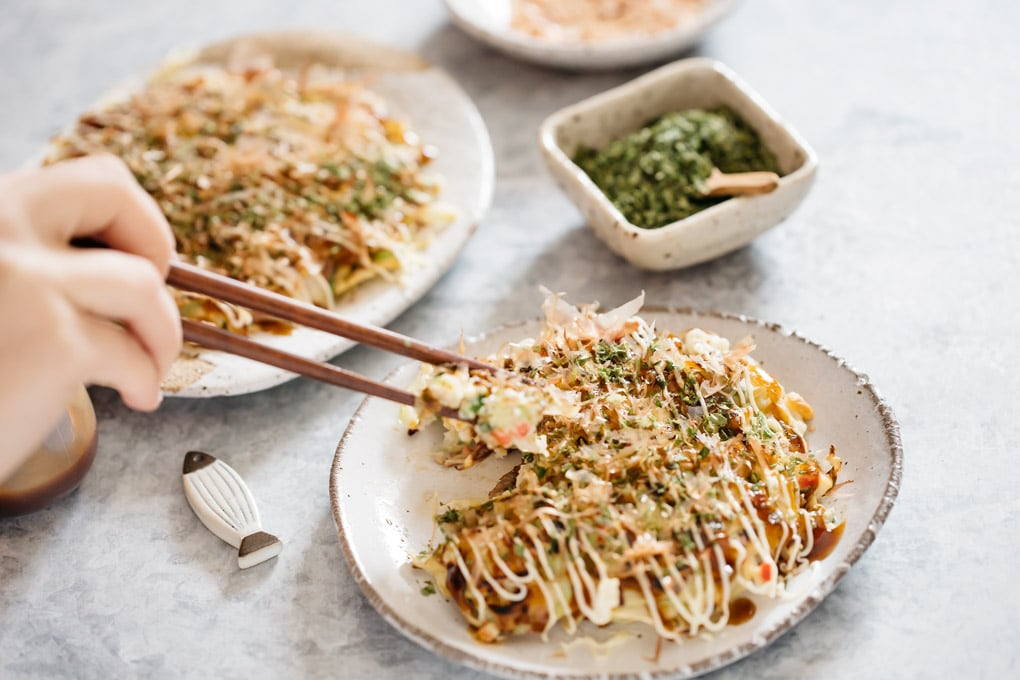 eaating okonomiyaki on a plate with a pair of chopsticks