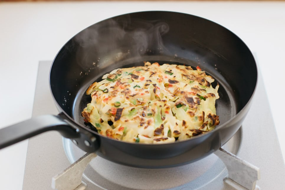 an okonomiyaki being cooked in a frying pan