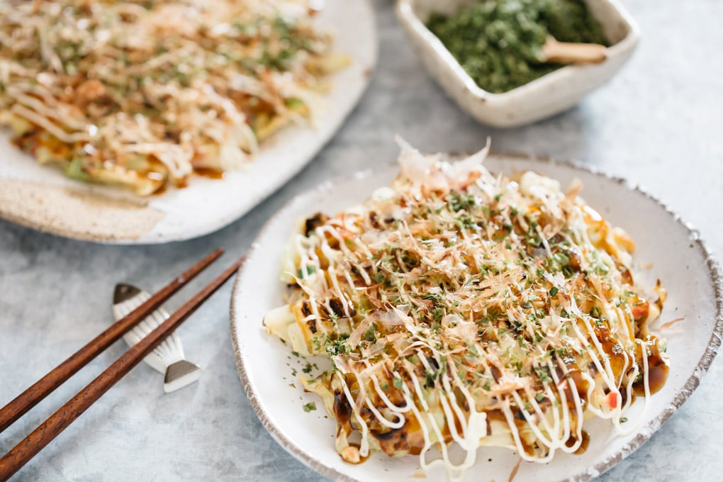 pork okonomiyaki served on two plates with a pair of chopsticks