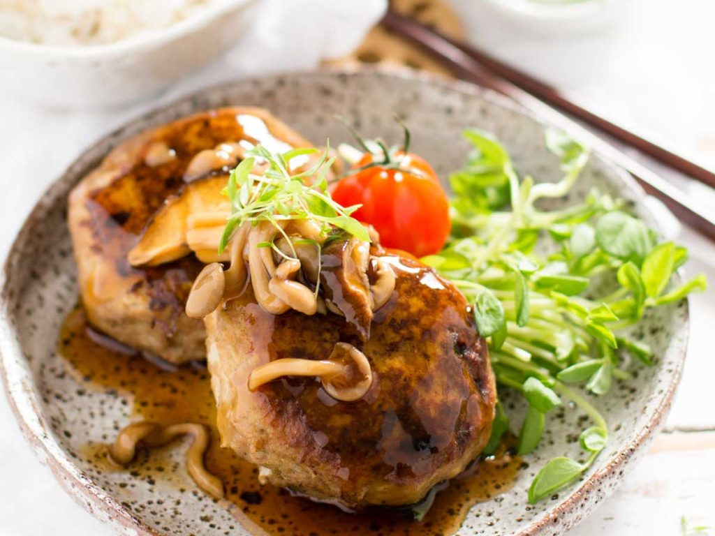 Japanese hamburger steak with mushroom sauce served on a plate with tomato and green salad