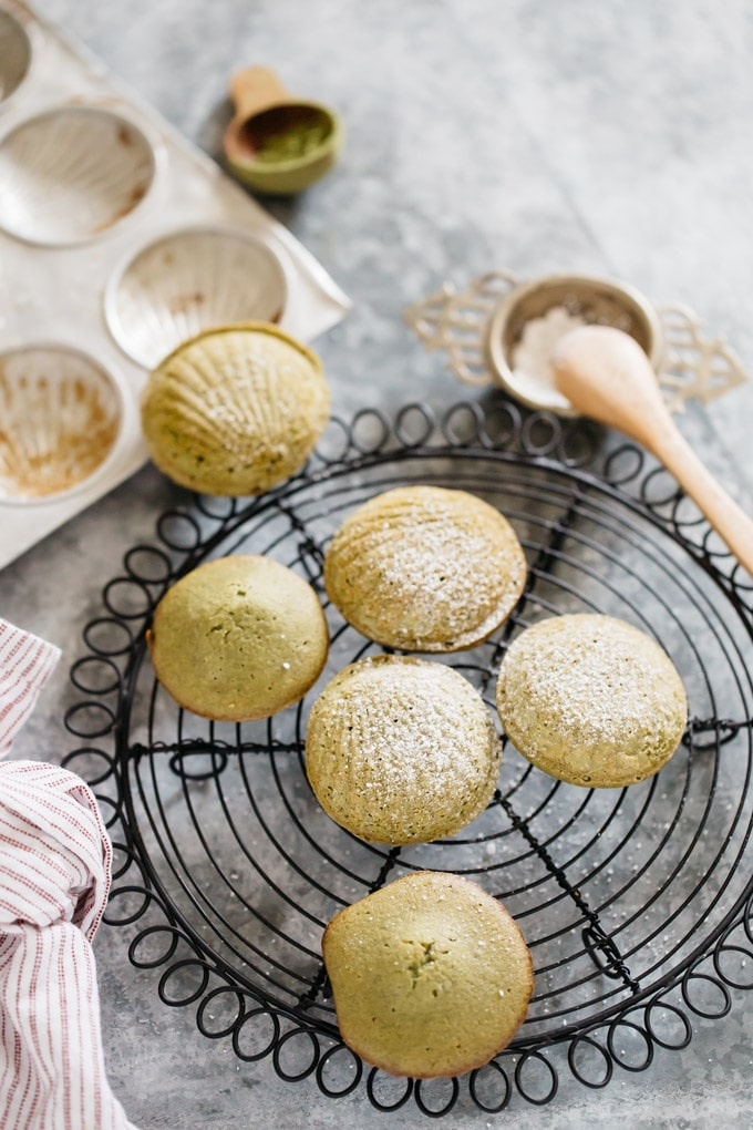 freshly baked matcha madeleine cooling on a black wire cooling rack
