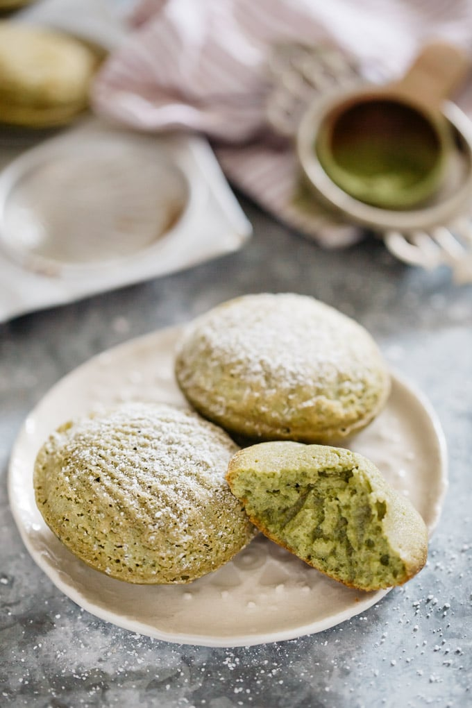 three matcha madeleines served on a small round plate and one is bitten.