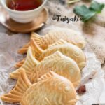 Three Taiyaki Japanese fish shaped waffle on baking paper with a cup of tea