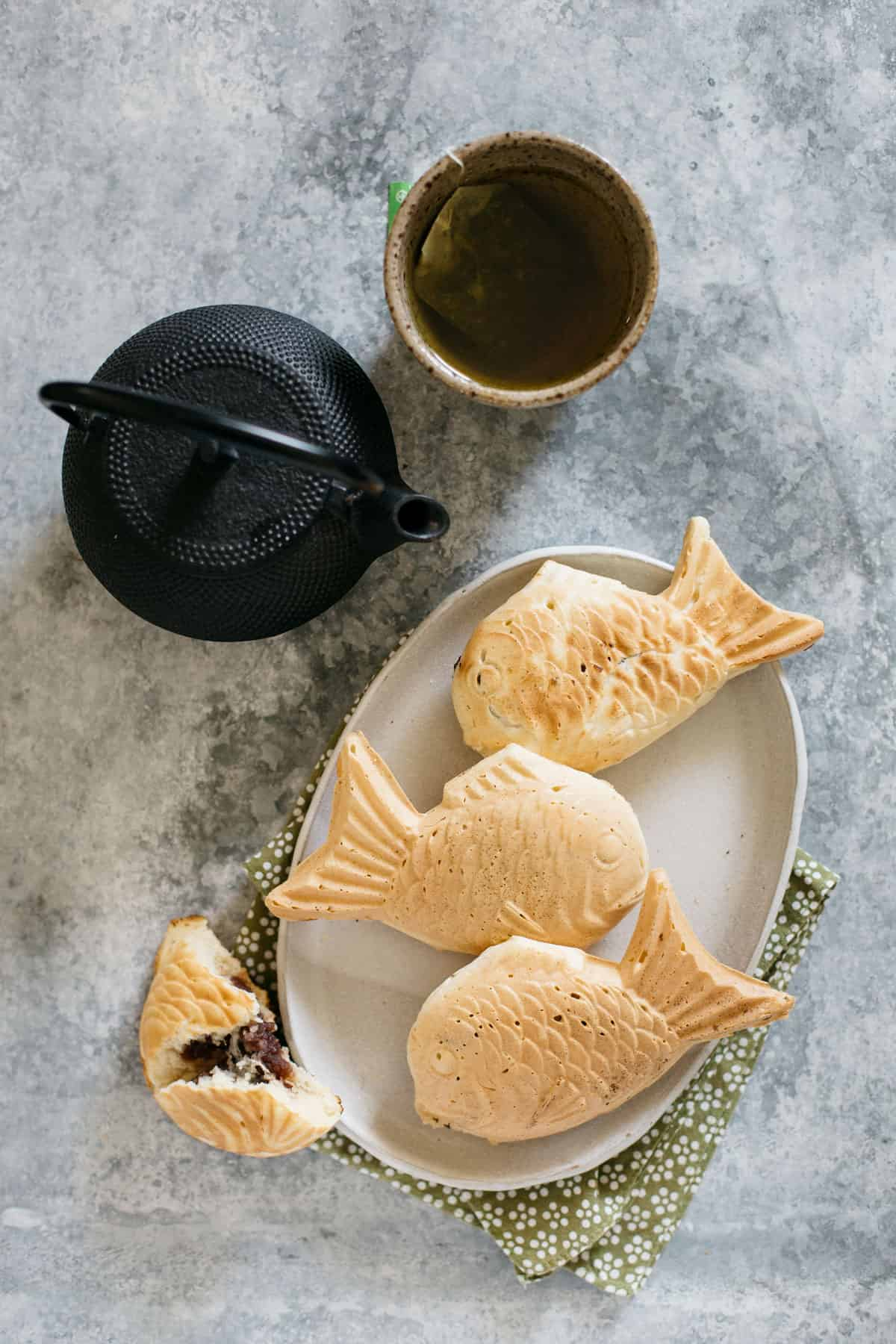 Three taiyaki fish waffle served on an oval plate with a Japanese steel kettle and a cup of green tea