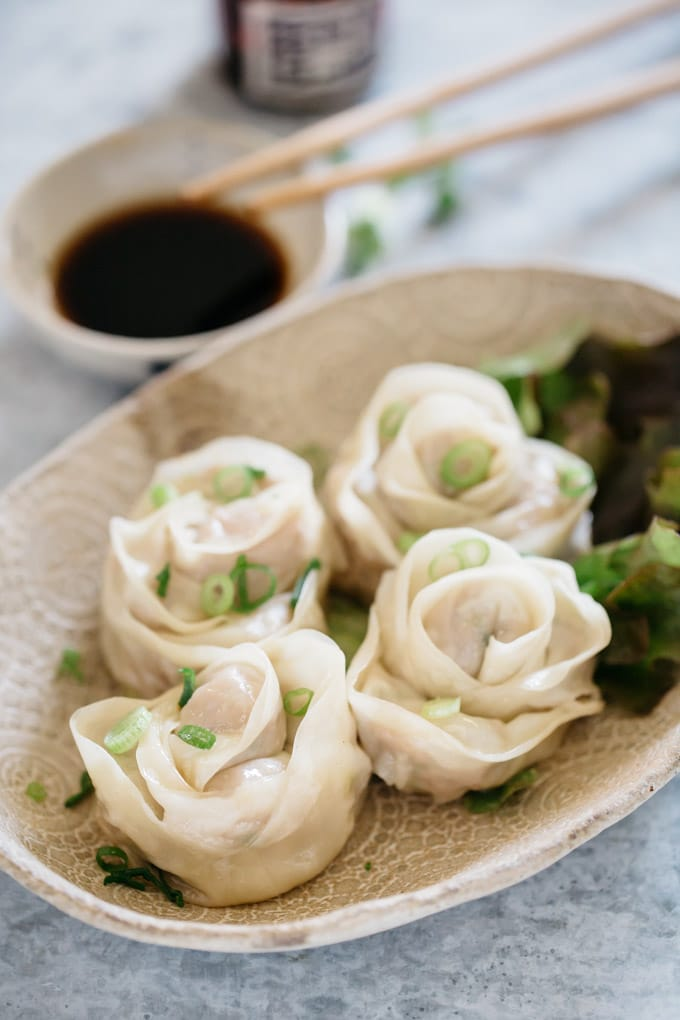 four rose shaped dumplings on an oval plate with a small dipping sauce and a pair of chopstick in backgound