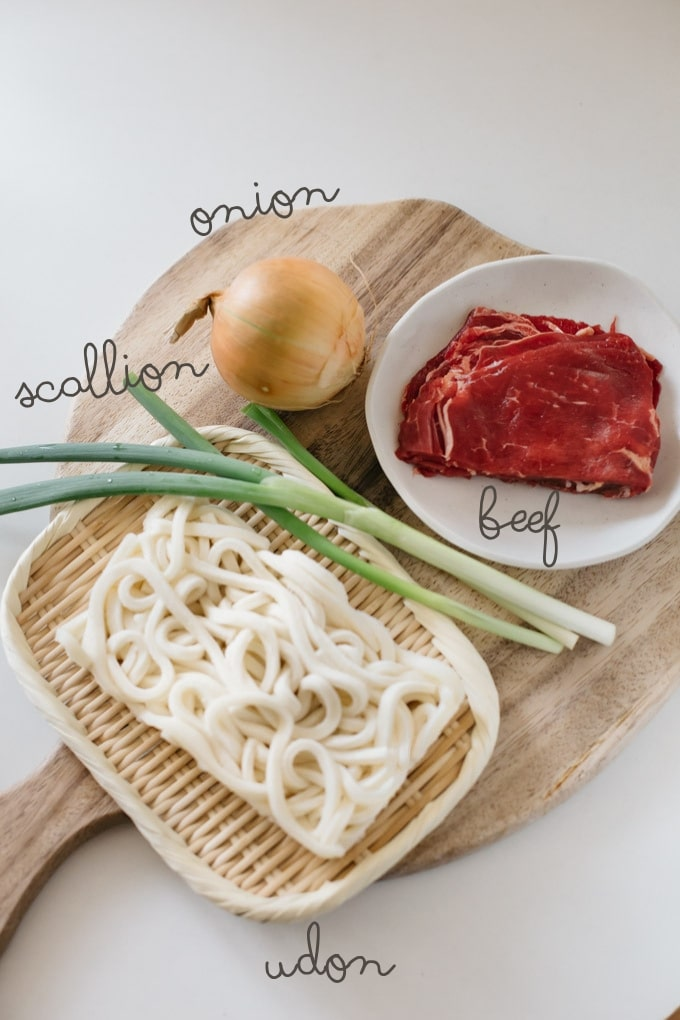 curry udon ingredients on a chopping board-udon noodle, thinly sliced beef, an onion, and scallions