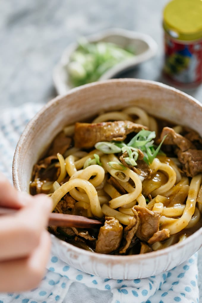 Curry udon served in a Japanese pottery bowl and a pair of copstick