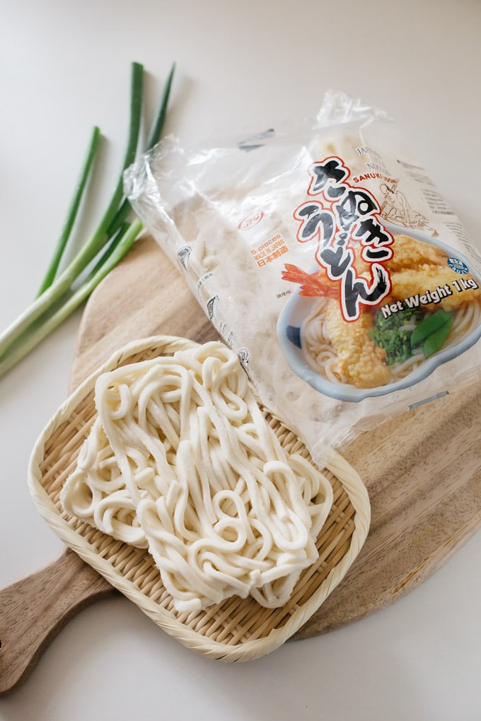 Udon noodle packet and udon noodle on a bamboo tray