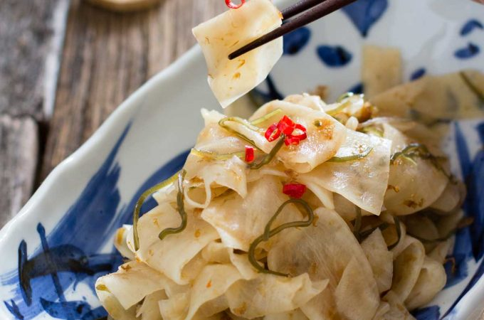 Pickled daikon radish picked up by a pair of chopsticks