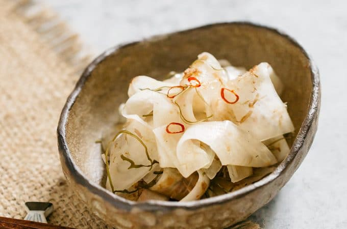 Pickled daikon served in an oval bowl with a pair of chopstick
