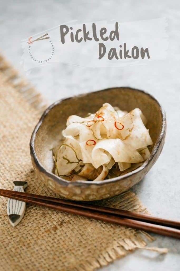 Tsukemono, pickled daikon served in an oval shallow bowl with a pair of chopstick
