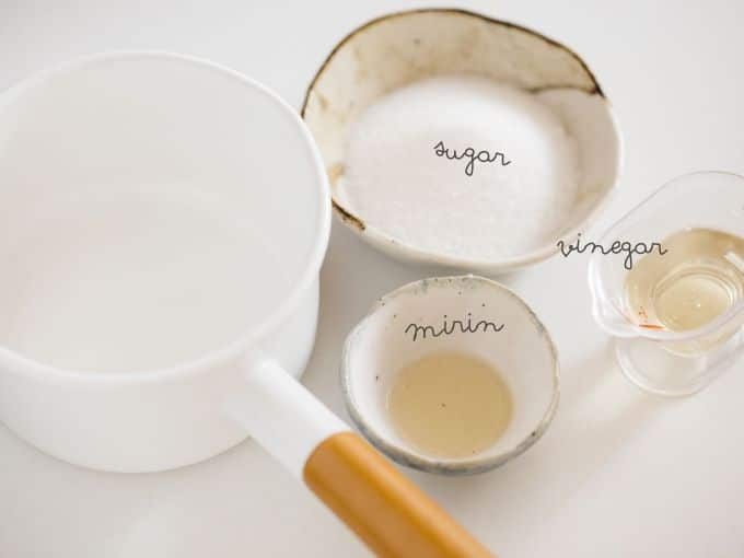 Sugar, mirin and rice vinegar in small bowls with a small saucepan
