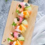 birds view of 3 sushi donuts on a wooden plate