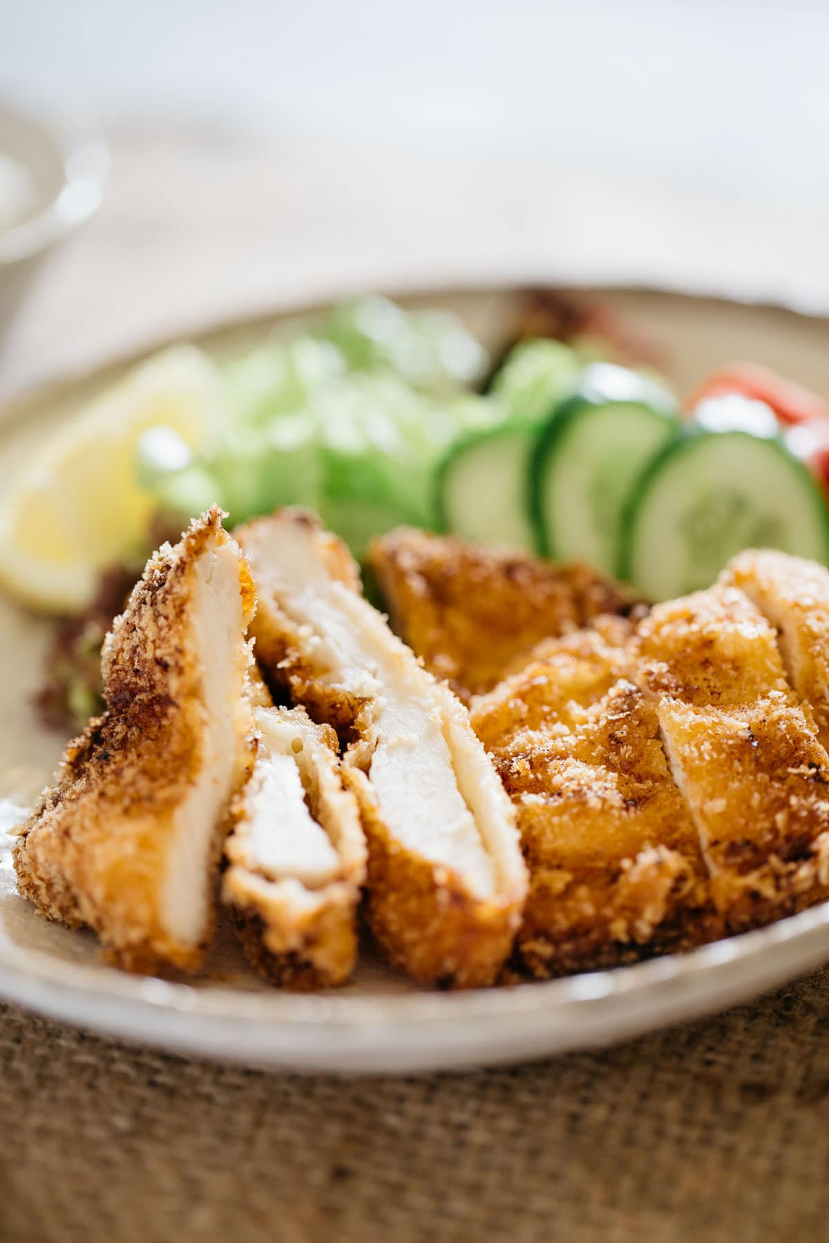 deep fried chicken katsu sliced and served on a plate with green salad