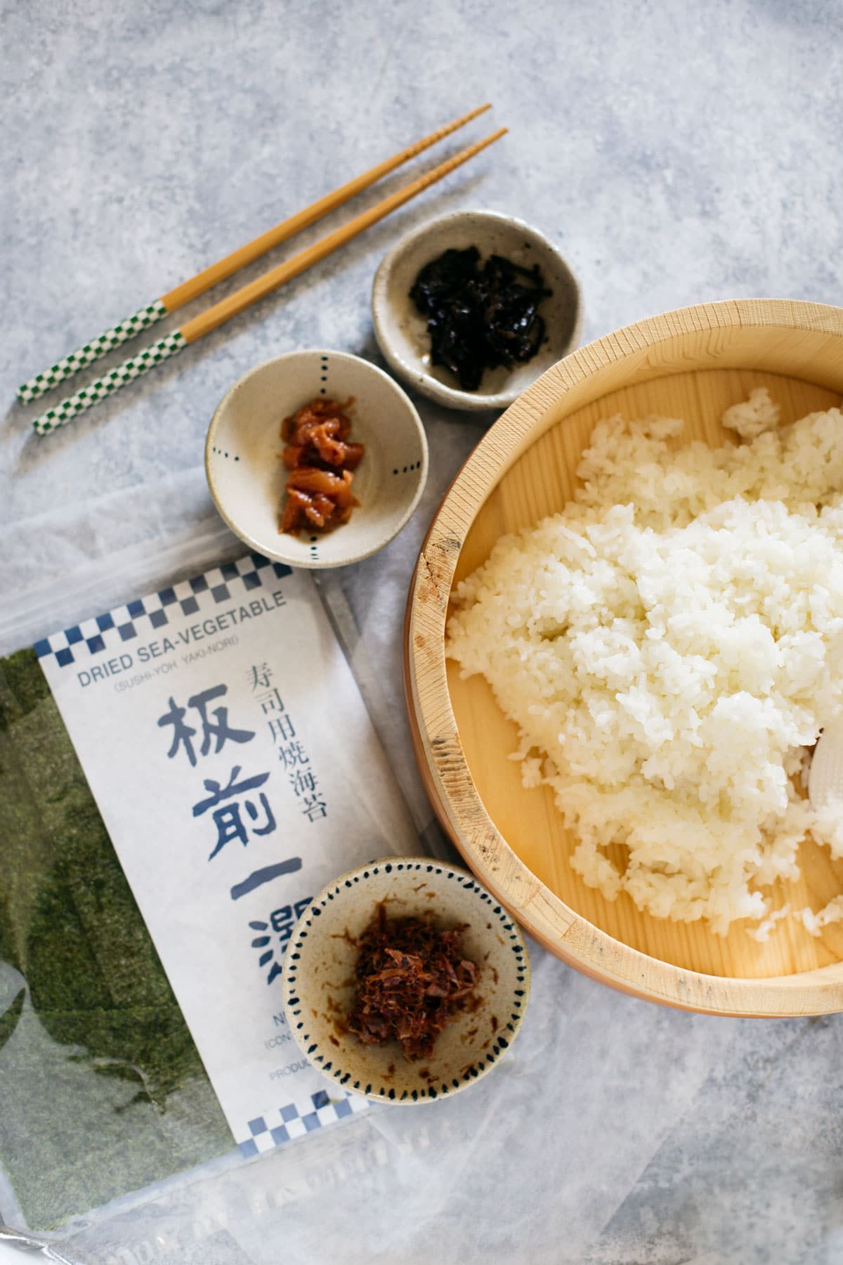 cooked rice in a wooden bowl, a pair of chopstick, three fillings, a packet of nori sheets