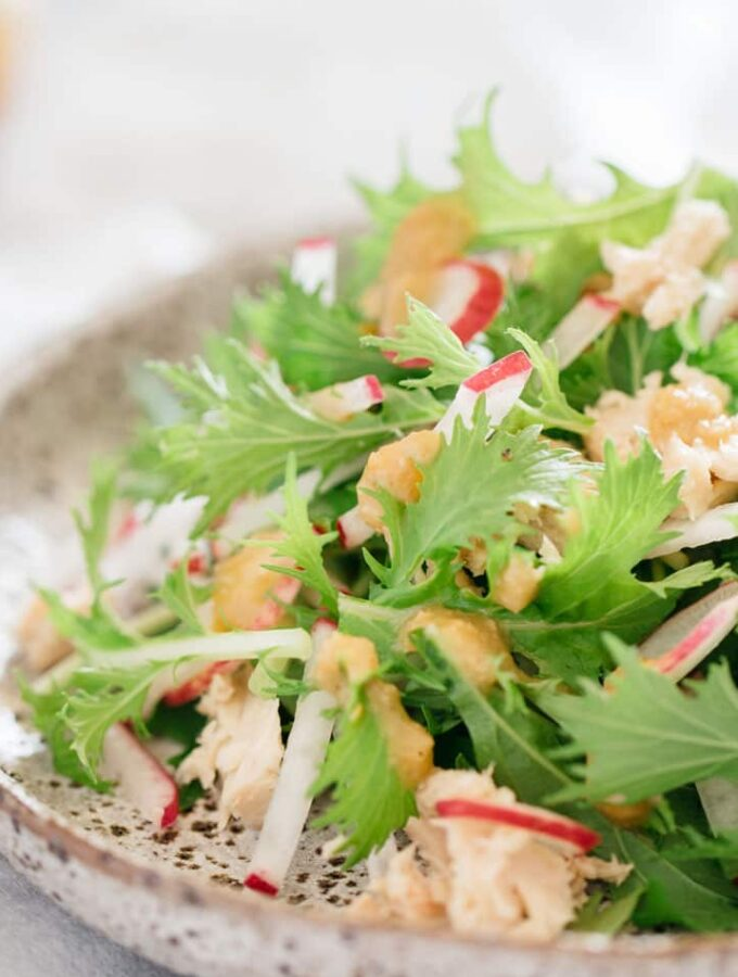 mizuna salad on flat plate with miso dressing in a glass jar