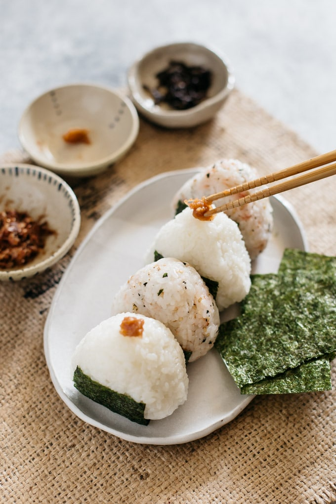 4 onigiri rice balls on a plate with nori seaweeds