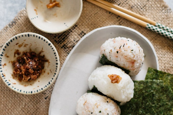 three onigiri rice balls on a plate and two small bowls of fillings