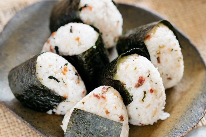 6 onigiri rice balls with seasonings on a plate
