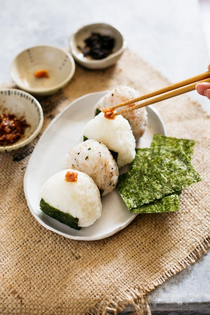 pickled plum being added on top of a Japanese rice ball with chopsticks