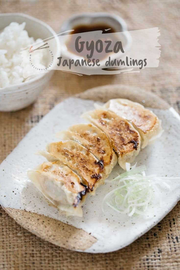 5 pieces of gyoza served on a rectangular shaped plate with a bowl of rice and dipping sauce