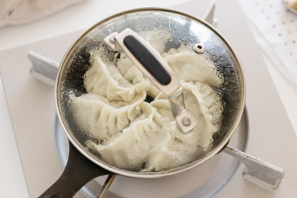 seven dumplings being steam fried in a cast iron skillet with a lid on