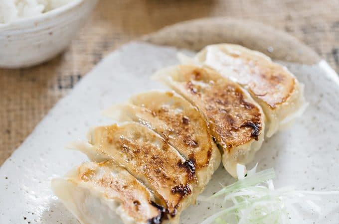 5 gyoza pieces served on a rectangle plate with a bowl of rice and dipping sauce