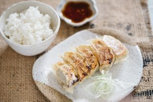 gyoza served on a plate with a bowl of rice and gyoza sauce